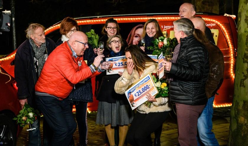 Ebru uit Schiedam wordt verrast door Postcode Loterij-ambassadeur Gaston Starreveld met de PostcodeStraatprijs-cheque en gloednieuwe BMW.