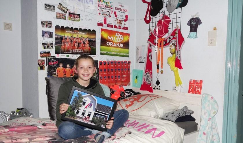 De 10-jarige Donna met in haar handen de foto van het Home Alone-huis, dat ze kreeg als herinnering aan haar deelname aan het programma.
