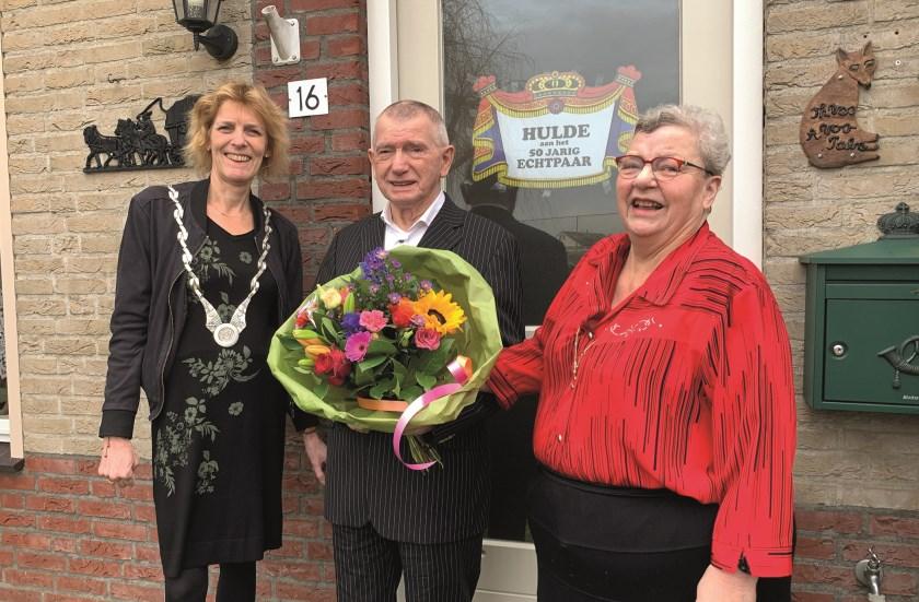 Loco-burgemeester Ineke Knuiman feliciteert Theo en Agnes Vos, terwijl de speciaal voor deze gelegenheid opgetrommelde Henk Nijland tot grote hilariteit van Agnes de foto maakt.