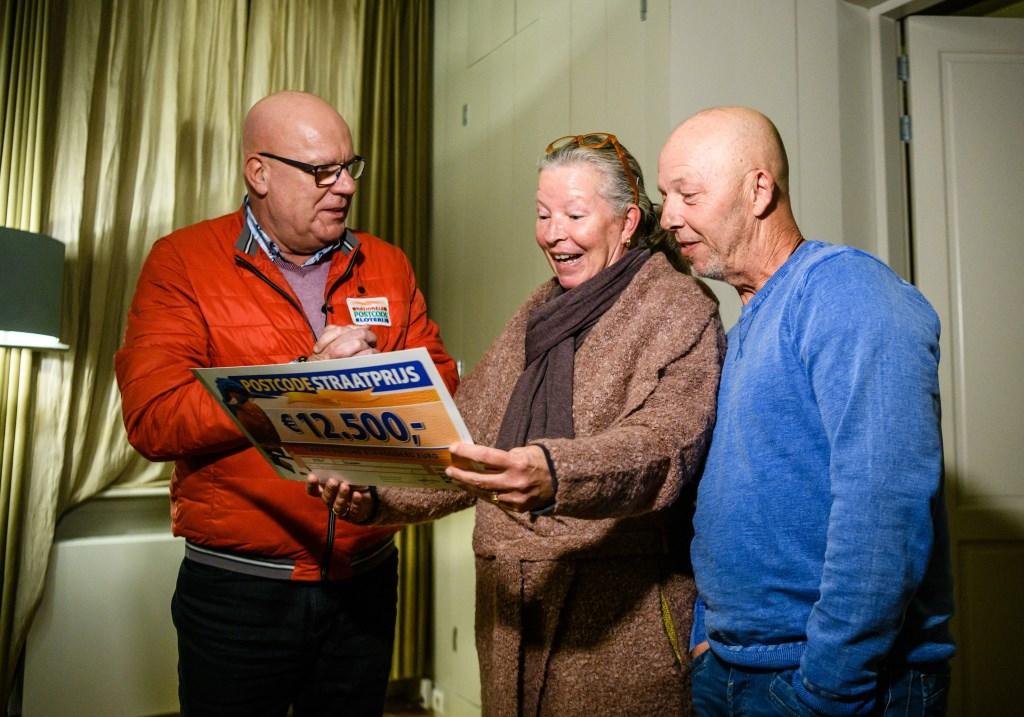 Hans en Marieke uit Schiedam worden verrast door Postcode Loterij-ambassadeur Gaston Starreveld met de PostcodeStraatprijs-cheque.  © DPG Media