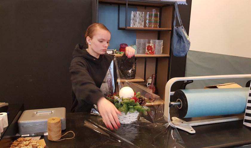 En weer is er een cadeautje verkocht bij Kado Lokaal. Serena van de Wardt pakt het kerststukje vakkundig in. (foto: Kees Stap)