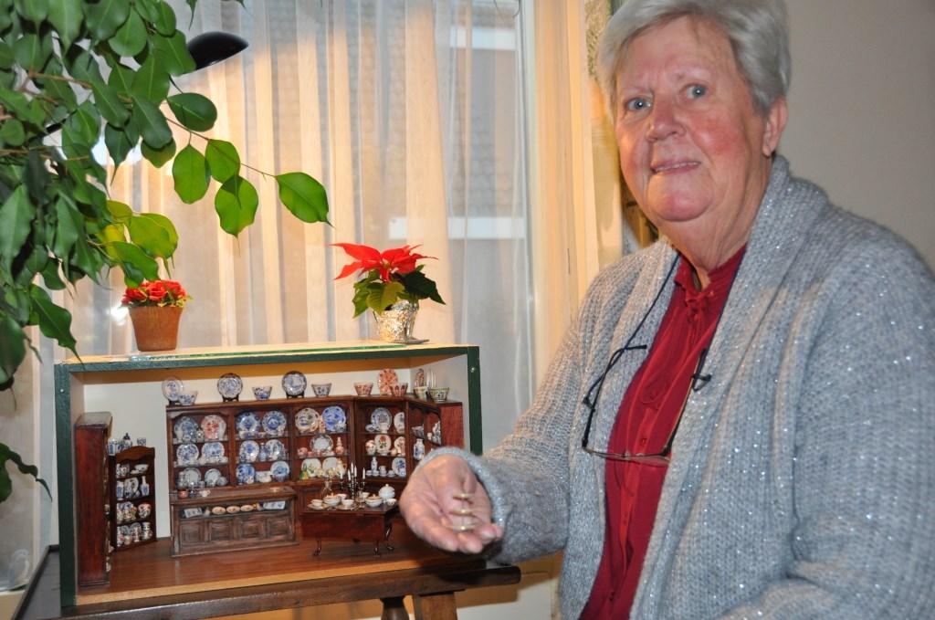 Cocky bij haar miniatuur porselein winkeltje. Elk serviesstukje is door haar gemaakt en beschilderd. Foto:  © DPG Media