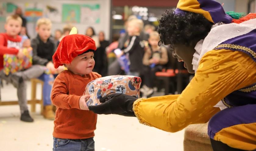 Zwarte Piet deelt cadeaus uit aan de Nikantes kinderen