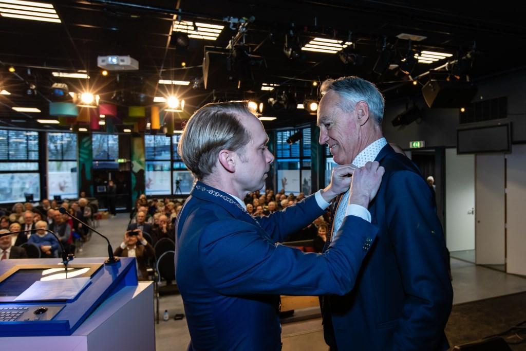 Burgemeester Gerdo van Grootheest speldt directeur-bestuurder Joost van Rijn de stadsspeld op. Foto: Jord Visser © DPG Media