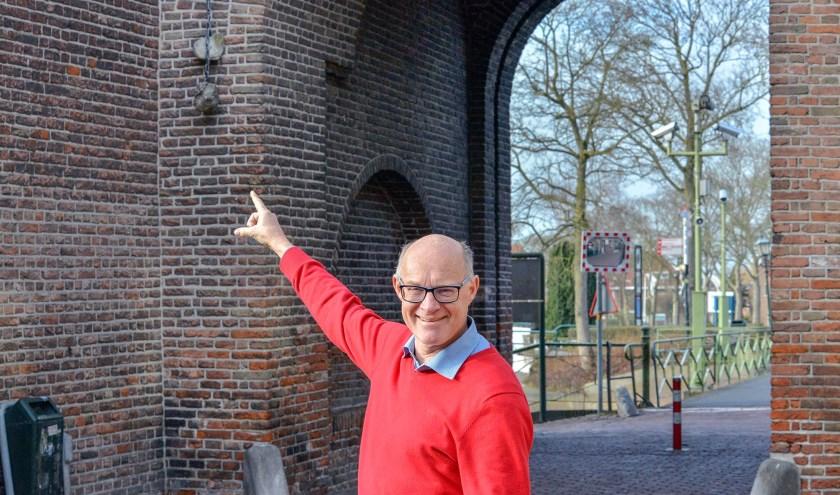Peter Versloot wijst naar de schandstenen die aan de stadspoort naast het oude stadhuis hangen.