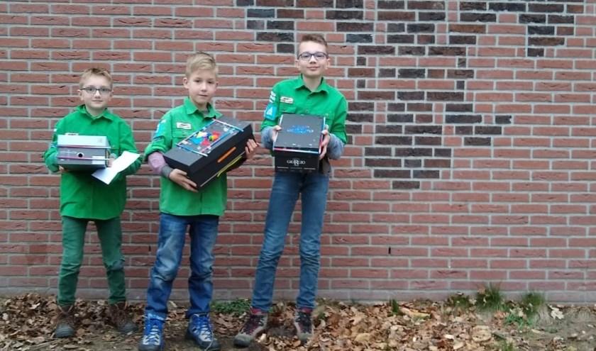 Hidde, Joah en Jelle die de doos laten zien, die ze voor de vluchtelingen hebben gemaakt. (Foto: Melchior Paans)