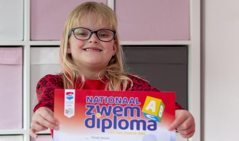Nienke Janssen (6) uit Lobith laat trots haar Nationale zwemdiploma A zien. (foto: Bas Bakema)