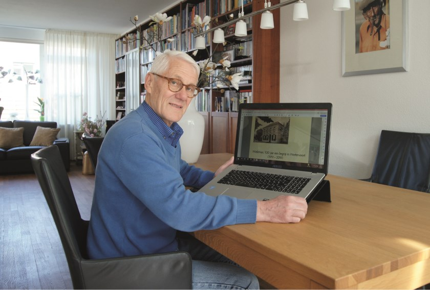 Wim Vlijm achter zijn computer met daarop een afbeelding van de cover van het boek 'Wieleman, 100 jaar een begrip in Westervoort', dat hij samen met andere leden van de Historische Kring schreef.