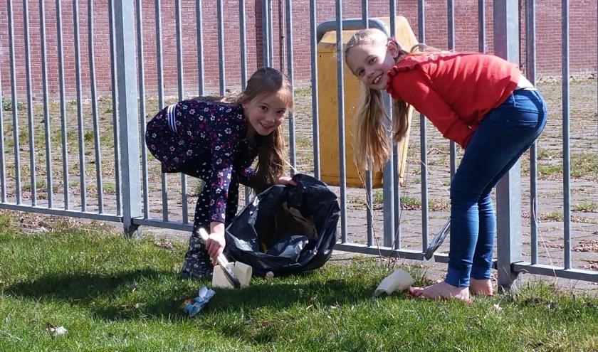 Zoey (r) en Anouk (l) zijn druk bezig met hun wekelijkse, zelfopgelegde taak om al het zwerfafval op te ruimen in de buurt.       FOTO: THEO RIETVELD