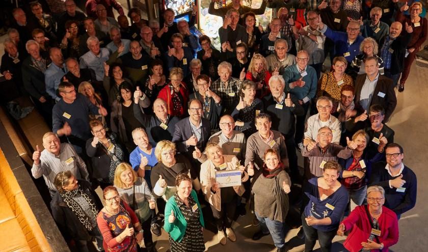 De vrijwilligers, met midden vooraan  Nicole Jorna (met Duim en oorkonde) en schuin links achter haar Henri Swinkels. FOTO: WIM HOLLEMANS