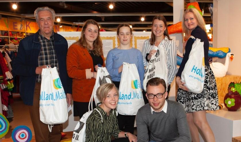 Wim Bakker (links) bedankt de studenten met een duurzame tas, gemaakt van afgedankte banners. (Foto: Jan-Fotografie)