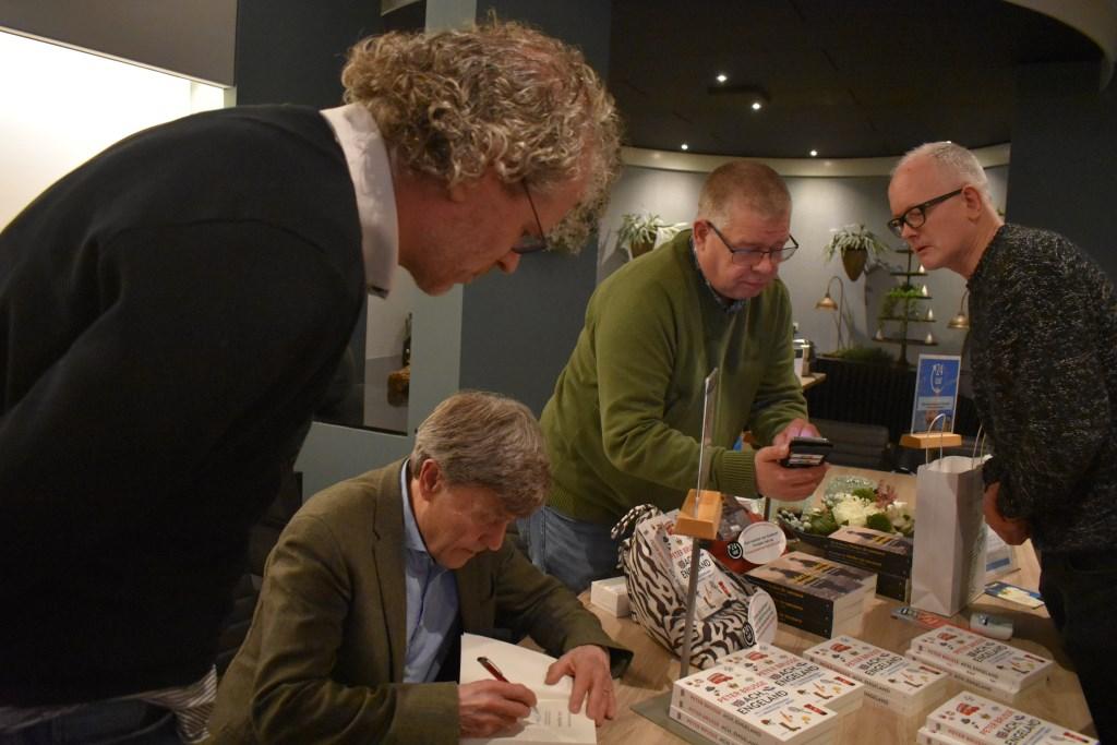 Uiteraard had Brusse de tijd om zijn boek te signeren. Hier met schrijver Frank Krake van het boek 'De Laatste Getuige'. Op de achtergrond John Reterink en de bezoeker uit Amsterdam. Foto: Jolien van Gaalen. Foto:  © DPG Media
