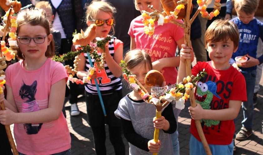 Kinderen lopen trots met hun zelfgemaakte palmpasenstokken mee in de optocht door Hellendoorn.
