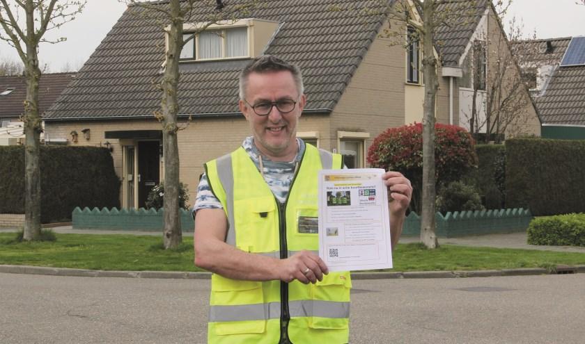 André Kok van het buurtpreventieteam van Wijkraad Duiven-West met een flyer waarmee hij nieuwe vrijwilligers probeert te werven.