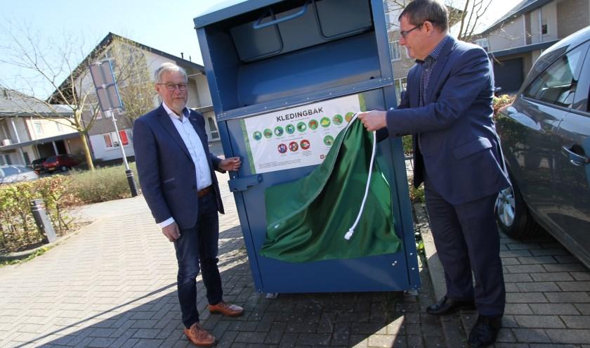 Driek van de Vondervoort en wethouder Hans van de Looij onthullen de nieuwe sticker op de container bij de mfa Noord. FOTO: Ad Adriaans.