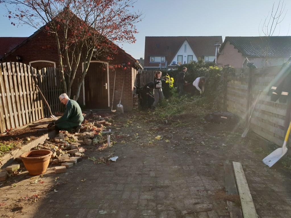Vrijwilligers van een kerk ruimen de tuin op Foto: Present Doetinchem © DPG Media