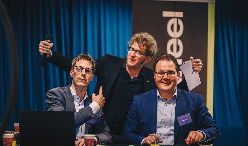 Moderator Martijn van Heese (midden) met  Wouter van den Bosch (accountant van KPMG) en notaruis Martijn de Jong van het Notarieel. Zij noteren de waarde van de gesloten matches.
