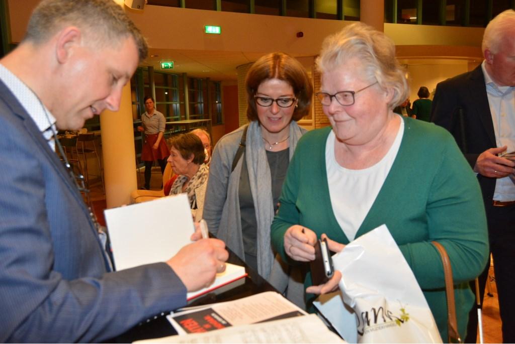 De auteur signeert de eerste exemplaren. Die avond werden er 140 boeken verkocht.  © DPG Media