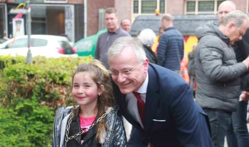 De burgemeester knipte een lint door samen met verschillende kinderen uit de straat
