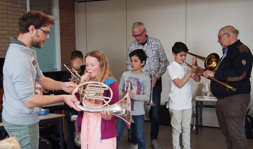 Muzikanten van Harmonie Unisono instrueren enkele leerlingen van de Roncallischool.