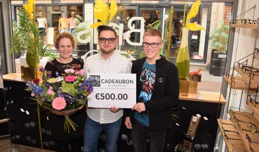 Winnares Laura Meijer (links), neemt samen met haar zoon Thijs (rechts), de cadeaubon van 500 euro in ontvangst.  (Foto: Janet Kooren)