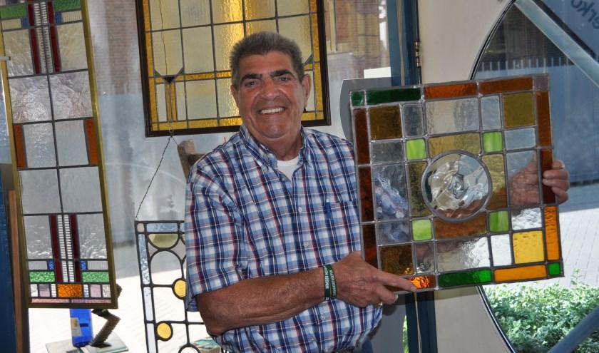 Jan Klok laat een glas-in-lood paneel zien dat hij zelf gemaakt heeft. FOTO: Julie Houben