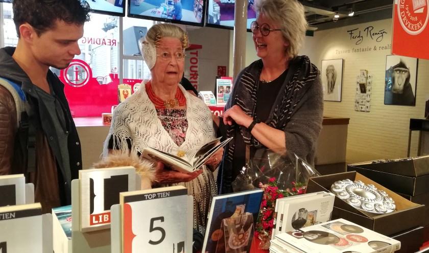 Michiel Poppe, koper van het 25.000ste  bakboek, Martine (96 jaar) staat met foto in het boek en Tinka Leene, schrijfster. Foto: Conny den Heijer