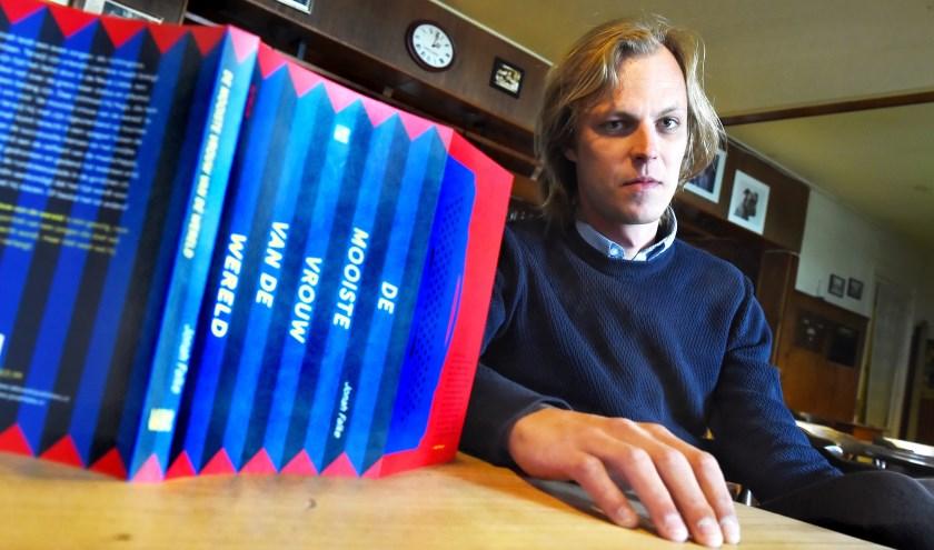 """Jonah Falke met zijn nieuwe boek in de kroeg van Michel Gervers. """"Ik voel me eigenlijk nergens thuis."""" (foto: Roel Kleinpenning)"""