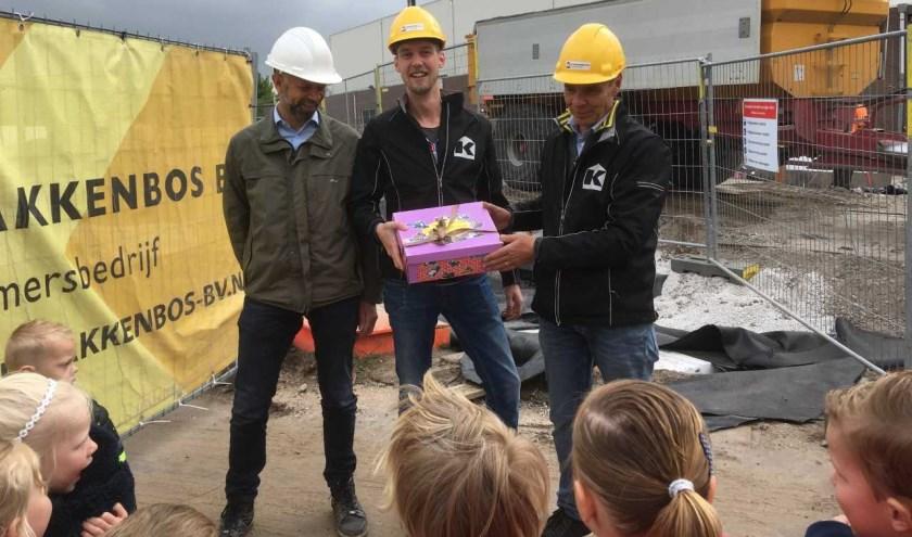 De kleuters geven de doos met tekeningen en kleurplaten aan de bouwvakkers.