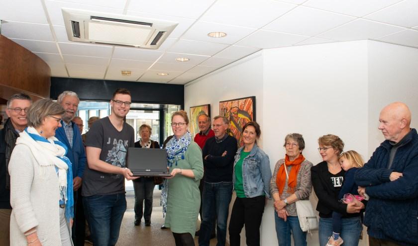Jarno Moeken, financieel adviseur bij de Rabobank Noord-Veluwe reikt een laptop uit aan Arnolde Spierenburg van de Stichting Present Epe-Heerde.