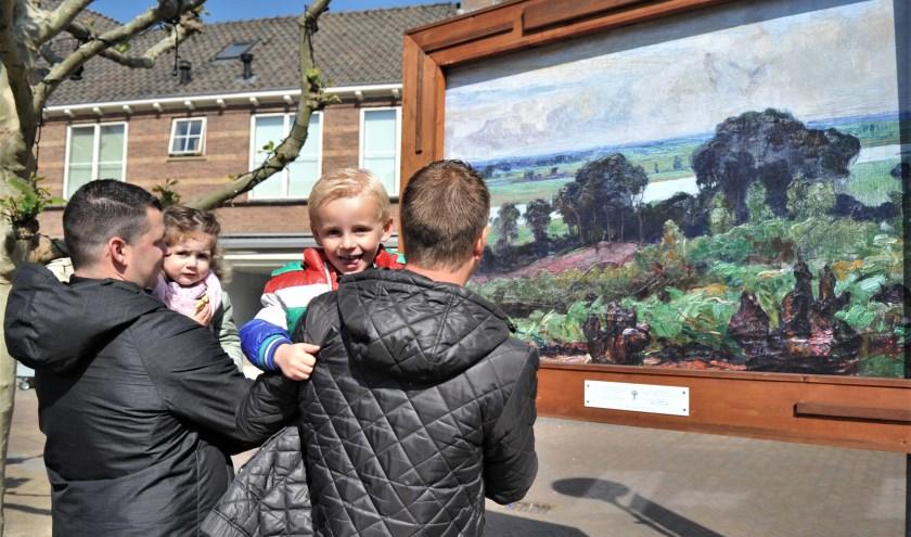Fenna en Job hadden op de armen van hun vaders meer belangstelling voor de fotograaf dan het prachtige doek. Foto: gertbudding.nl
