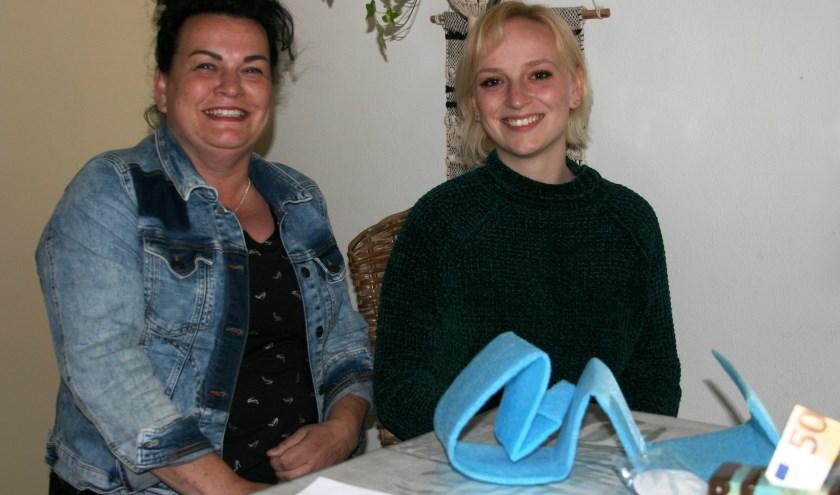 Nina en Isabelle Lindeboom terug in Tiel na hun verblijf in een Grieks vluchtelingenkamp. Op tafel een stuk van een blauw slaapmatje uit het kamp. (Foto: Corien Remijn)