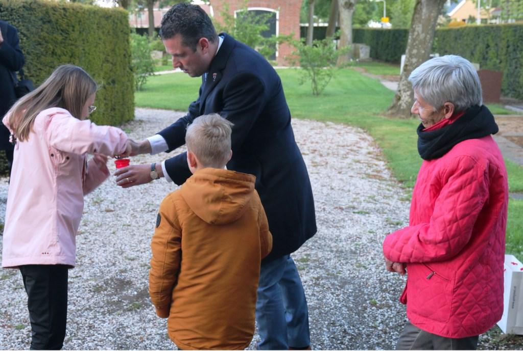 Jopie van Etten kijkt toe hoe Sebastian van Etten van de Oranjevereniging Westmaas de schoolkinderen helpt met het ontsteken van de herdenkingskaarsen. (foto: Conno Bochoven)  © DPG Media