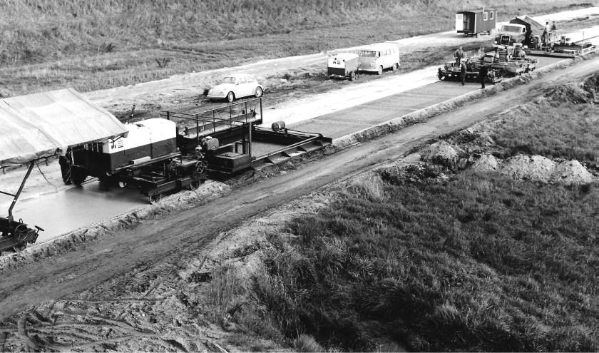 """Aanleg in 1965 van de Maasroute in Vlijmen. Het leggen van een betonnen wegdek met de zogenaamde """"betontrein"""". Foto: Collectie Nico de Bont"""