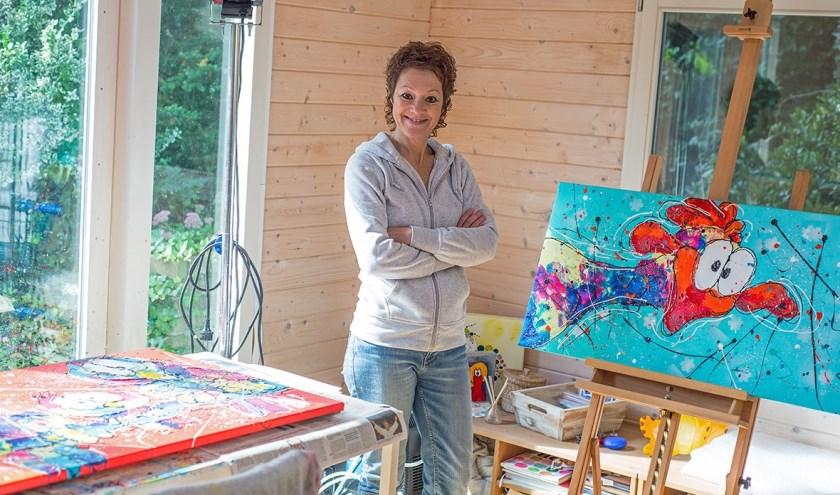 Ellen Moorman in haar atelier met een blij doek. (foto: PR)