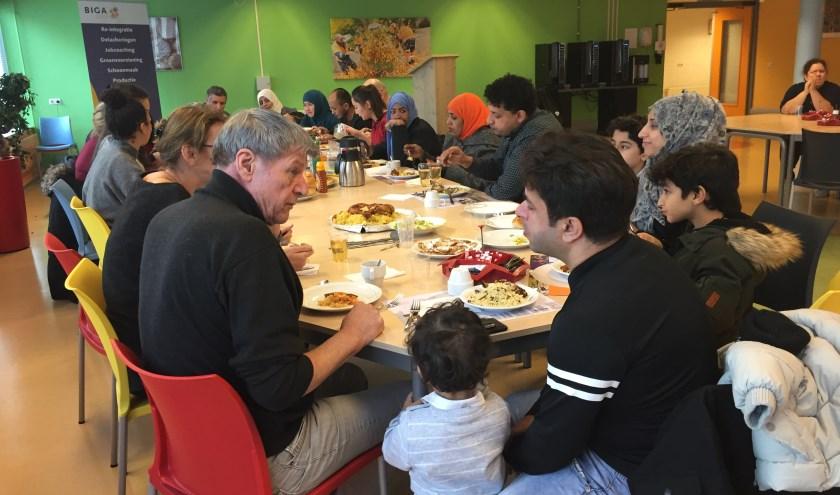 Een indruk van de lunch die VWMN eerder dit jaar hield. Op de foto nieuwkomers, andere inwoners van Zeist, vrijwilligers en beroepskrachten van VWMN. Gezamenlijk gebruikten zij de maaltijd waarbij iedereen iets mee had gebracht uit het eigen land. De sfeer was optimaal. Op 20 juni is er weer zo'n bijeenkomst.