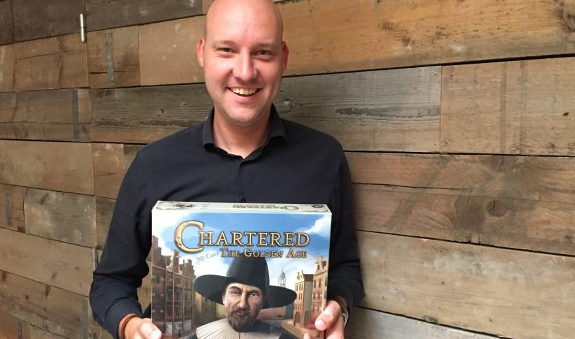 Arnold van Binsbergen heeft het spel in zijn handen dat hij samen met Alexander Kneepkens heeft gemaakt. (Foto: Nanda van Heteren)