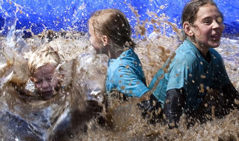 """Het kan de meeste kinderen niet nat of modderig genoeg zijn. Ze genieten met volle teugen en zijn vaak teleurgesteld als ze over de eindstreep komen. """"Is het nu al klaar?"""" Foto: Jan Broekman."""