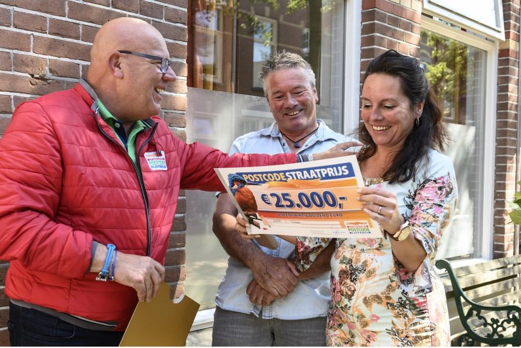 Madelon en haar man Theo nemen de PostcodeStraatprijs-cheque ter waarde van 25.000 euro in ontvangst van Gaston. Jurgen Jacob Lodder © DPG Media