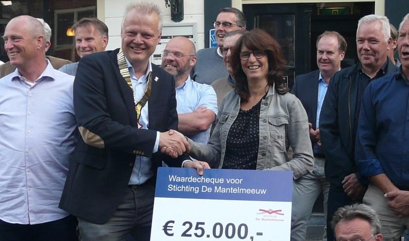 Wouter Verboon reikt een cheque van 25.000 euro uit aan Mirjam Bijlenga van stichting De Mantelmeeuw.
