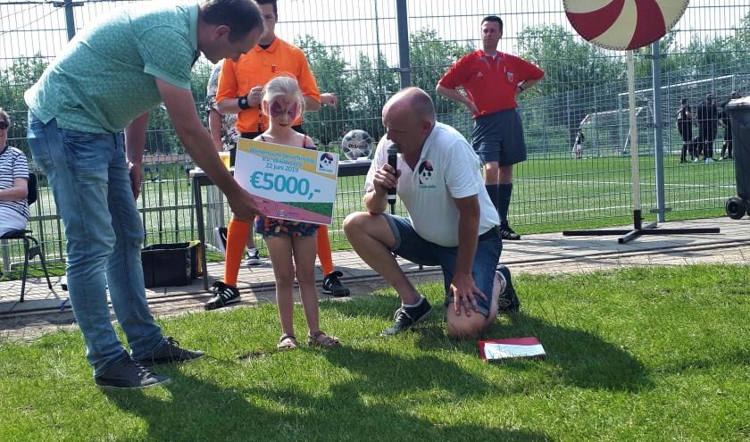 Lotgenootje Ninte Dirkx ontvangt een cheque van 5000 euro van Martin Slooijer, de hoofdsponsor van de wielertocht. (foto: pr)