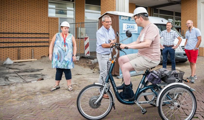 Nog even en Jeroen van Dongen kan zijn fiets parkeren in een nieuwe, ruimere stalling bij appartementencomplex Dorrestein in Nieuwerkerk aan den IJssel. Wethouder Jan Verbeek feliciteert hem daar alvast mee. Evelien van der Vlist (links) gaat haar nieuwe elektrische driewielfiets bestellen. Die kon pas komen als hij binnen gestald kan worden.