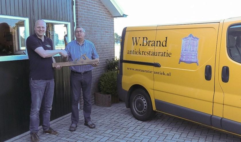 Henkjan Beekhof (l) heeft het bedrijf van Willem Brand overgenomen gesymboliseerd door de overdracht van de grote schaaf.