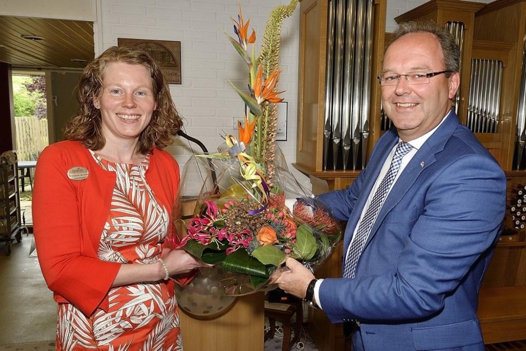 Dhr. Stoop overhandigd Marianne de Vries een mooi bloemstuk. Foto: Jan van Arend © DPG Media