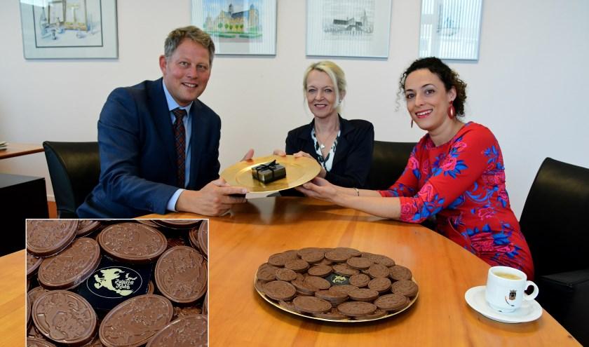Marjo en haar dochter Najah (r) met de burgemeester en het chocolaatje in souvenir verpakking. Foto: Jan Wijten