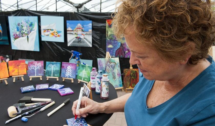 Marianne Blom heeft op de tafel schilderijen in broekzakformaat staan. Ze maakt ook grote doeken. (foto: Ellen Koelewijn)