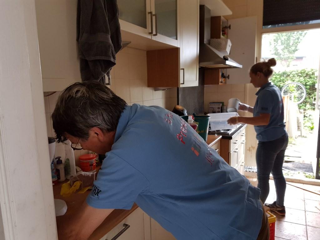 Twee vrijwilligers ruimen de keuken op en maken alles schoon Foto: Present Winterswijk © DPG Media