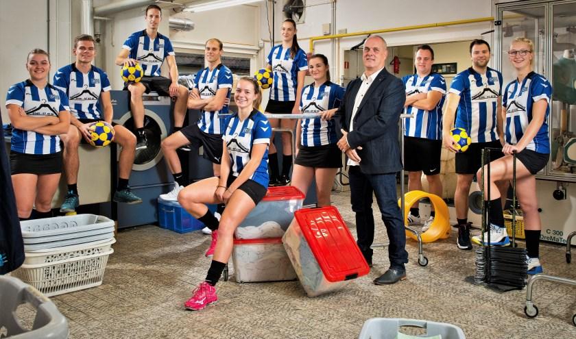 De trainer van Animo, Wim Jansen, te midden van zijn speelsters en spelers van het vlaggneschip van de korfbalvereniging. (Foto Mark Verweij)