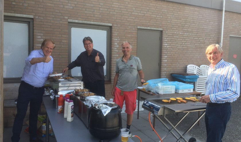 De enthousiaste vrijwilligers van de Lionsclub staan klaar achter de barbecue.