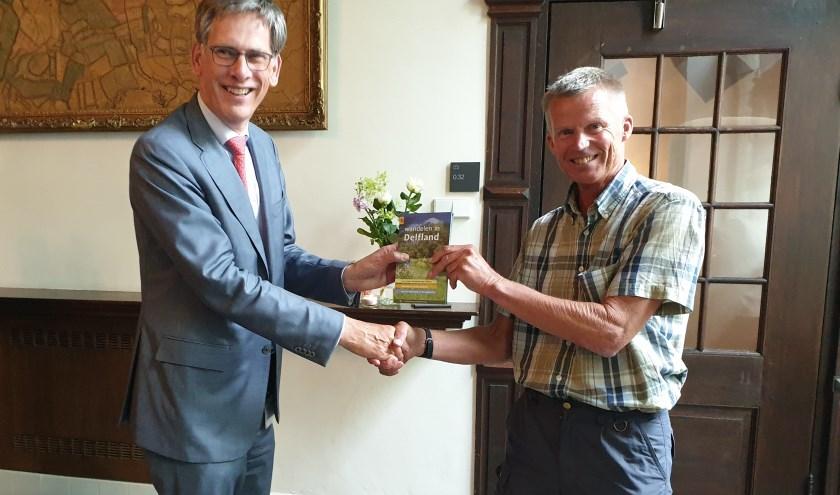 Auteur Cock Hazeu overhandigt het eerste exemplaar van Wandelen in Delfland aan dijkgraaf Daverveldt.